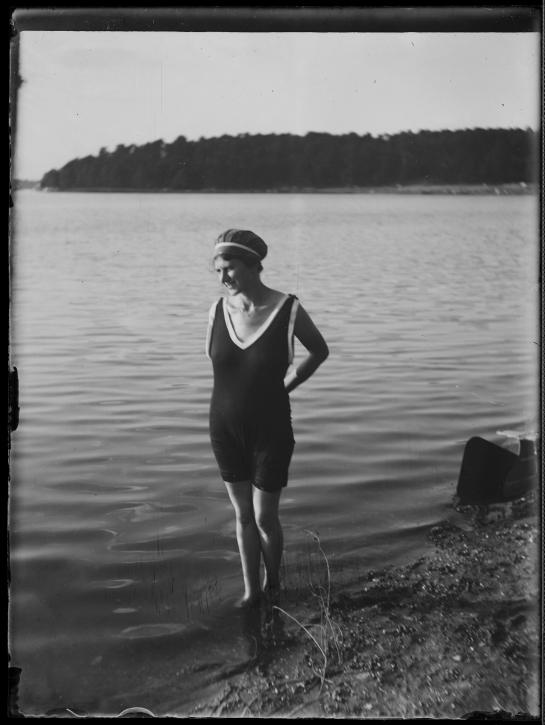 Woman standing at the edge of a lake in bathing suit. This image is originally a negative on glass. It was digitalized with a Nikon D2X and a macro lens.