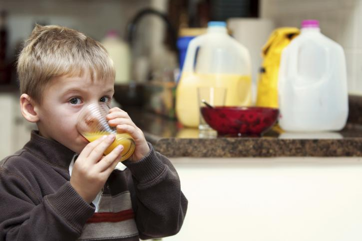 a young boy drinking his orange juice in the early morning before heading off to school