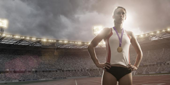Female athlete standing in floodlit athletics stadium wearing gold medal