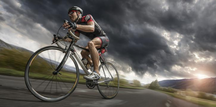 A low angle view of a professional male cyclist riding on a flat deserted road through mountainous terrain under a dark and stormy evening sky at sunset. The cyclist is wearing generic cycling suit, cycling helmet and sunglasses and is riding a generic unbranded road racing bike. With motion blur.