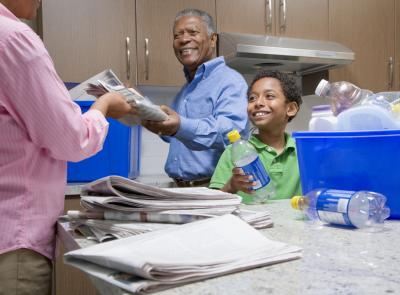 Grandparents Recycling With Grandson in Kitchen