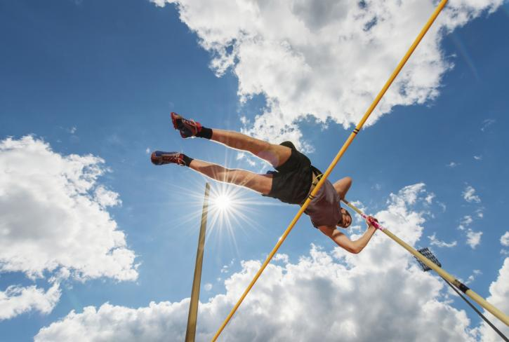 Low angle view of a young man making an effort at pole vault competition.