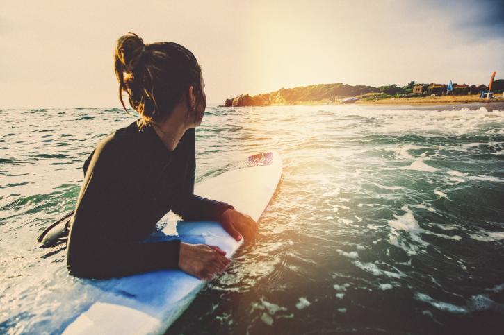 Young woman floating on her surfboard, while resting from surfing