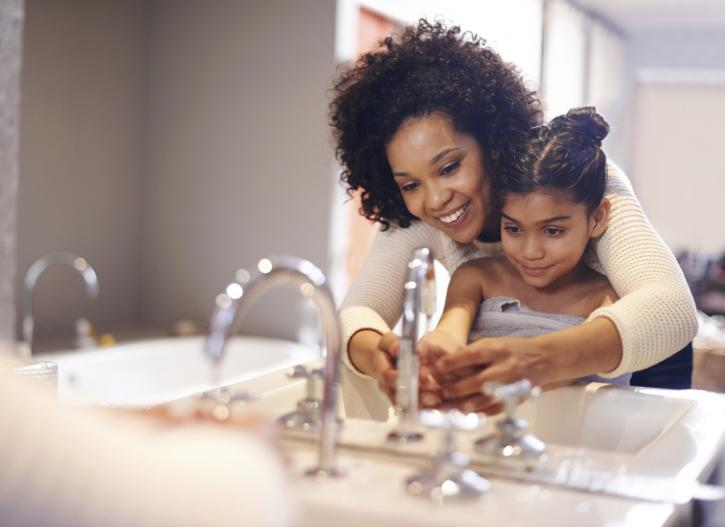 Cropped shot of a mother and daughter washing their hands at the bathroom sink
