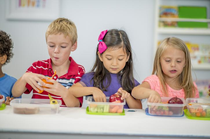 A multi-ethnic group of elementary age children are sitting at their desks and are eating their healthy lunches.