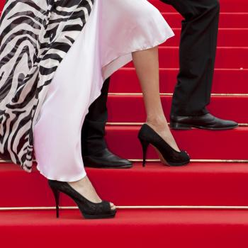 Feet of a glamorous couple on red carpet