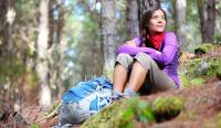 Woman hiker sitting in forest, hiking