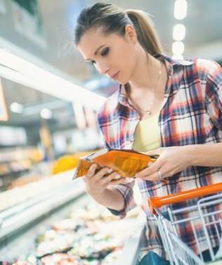 Woman in grocery store with shopping basket holding frozen food in plastic packaging