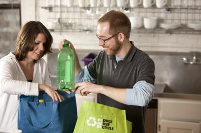A couple recycles plastic bottles in the kitchen.