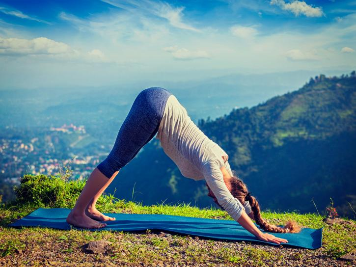 Young sporty fit woman doing yoga outdoors in mountains