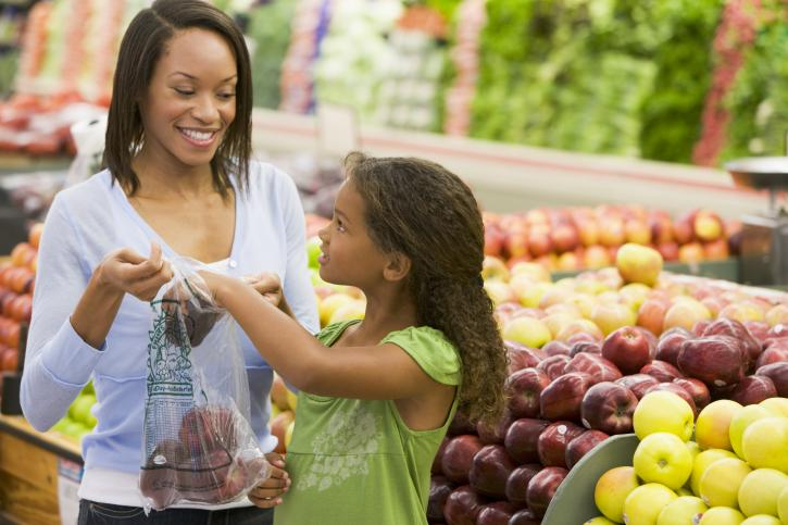 Mother and daughter in produce section of grocery store using plastic bag for fruit