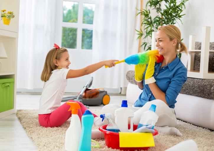 Mother and daughter spring cleaning in living room