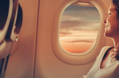 Woman sitting in airplane looking out the window