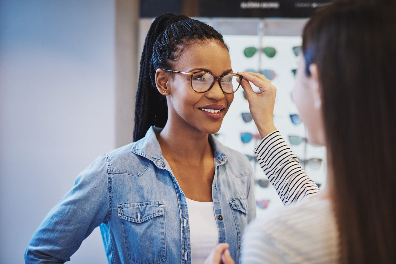 Doctor fitting plastic eyeglass on a woman