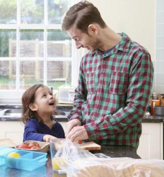 Father making sandwich with child