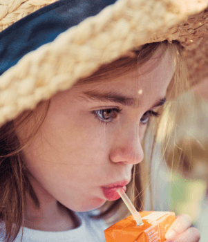 girl sipping juice box, plastic straw